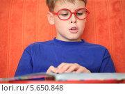 Купить «Мальчик в очках внимательно читает книгу», фото № 5650848, снято 19 октября 2011 г. (c) Losevsky Pavel / Фотобанк Лори
