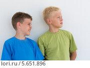 Купить «Два мальчика в цветных футболках на фоне белой стены что-то разглядывают», фото № 5651896, снято 7 июля 2012 г. (c) Losevsky Pavel / Фотобанк Лори