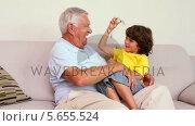Купить «Senior man sitting on couch with his grandson », видеоролик № 5655524, снято 23 августа 2019 г. (c) Wavebreak Media / Фотобанк Лори