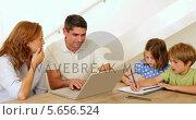 Купить «Parents using laptop and children colouring at the table», видеоролик № 5656524, снято 23 августа 2019 г. (c) Wavebreak Media / Фотобанк Лори