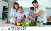 Купить «Smiling family preparing a healthy dinner together», видеоролик № 5656624, снято 23 августа 2019 г. (c) Wavebreak Media / Фотобанк Лори