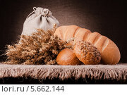 Купить «Свежий хлеб, мешок муки и колосья на темном фоне», фото № 5662144, снято 26 февраля 2013 г. (c) Natalja Stotika / Фотобанк Лори