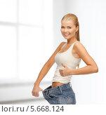 Купить «Стройная девушка демонстрирует джинсы большого размера», фото № 5668124, снято 23 марта 2013 г. (c) Syda Productions / Фотобанк Лори