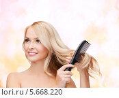 Купить «Очаровательная блондинка расчесывает волосы и улыбается», фото № 5668220, снято 7 января 2014 г. (c) Syda Productions / Фотобанк Лори