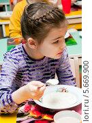 Купить «Девочка ест кашу в детском саду», эксклюзивное фото № 5669900, снято 28 февраля 2014 г. (c) Куликова Вероника / Фотобанк Лори