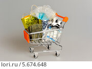 Купить «Пакеты с одеждой в магазинной тележке на сером фоне», фото № 5674648, снято 23 февраля 2014 г. (c) Алексей Карпов / Фотобанк Лори