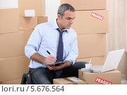 Купить «работник торгового склада среди картонных коробок», фото № 5676564, снято 28 октября 2010 г. (c) Phovoir Images / Фотобанк Лори