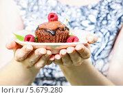 Купить «Женщина предлагает кекс с шоколадом и ягодами на тарелке», фото № 5679280, снято 19 июня 2019 г. (c) BE&W Photo / Фотобанк Лори