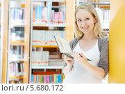 Купить «Улыбающаяся девушка с книгой в руках в библиотеке», фото № 5680172, снято 19 июня 2013 г. (c) Дмитрий Калиновский / Фотобанк Лори