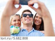 Купить «Счастливые друзья фотографируются на телефон на пляже и смеются», фото № 5682808, снято 31 августа 2013 г. (c) Syda Productions / Фотобанк Лори