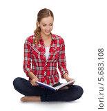 Купить «Юная девушка в повседневной одежде читает книгу, сидя на полу», фото № 5683108, снято 19 января 2014 г. (c) Syda Productions / Фотобанк Лори