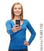 Купить «Милая девушка улыбается, фотографируясь на смартфон», фото № 5683132, снято 5 декабря 2013 г. (c) Syda Productions / Фотобанк Лори