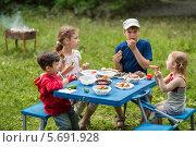 Купить «Четверо детей едят мясо с овощами на пикнике, сидя за раскладным столом», фото № 5691928, снято 2 июня 2013 г. (c) Losevsky Pavel / Фотобанк Лори