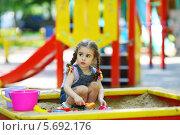 Купить «Маленькая девочка с косичками сидит в песочнице на детской площадке и играет с пластмассовыми совочками и формочками», фото № 5692176, снято 4 июня 2013 г. (c) Losevsky Pavel / Фотобанк Лори