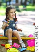 Купить «Портрет счастливой маленькой девочки, сидящей в песочнице на детской площадке летом», фото № 5692180, снято 4 июня 2013 г. (c) Losevsky Pavel / Фотобанк Лори