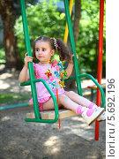 Купить «Счастливая маленькая девочка с хвостиками в розовом платье качается на качелях на детской площадке», фото № 5692196, снято 4 июня 2013 г. (c) Losevsky Pavel / Фотобанк Лори