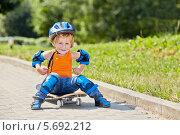 Купить «Маленький скейтбордист в защите сидит на скейтборде», фото № 5692212, снято 4 июля 2013 г. (c) Losevsky Pavel / Фотобанк Лори