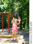 Купить «Маленькая девочка стоит в песочнице и бросает вверх песок на детской площадке в летний день», фото № 5692220, снято 4 июня 2013 г. (c) Losevsky Pavel / Фотобанк Лори