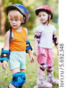 Купить «Двое детей в защитах и касках на роликах стоят на дорожке в летнем парке», фото № 5692348, снято 4 июля 2013 г. (c) Losevsky Pavel / Фотобанк Лори