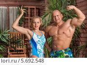 Купить «Девушка в купальнике и мускулистый мужчина позируют возле деревянного дома», фото № 5692548, снято 3 октября 2013 г. (c) Losevsky Pavel / Фотобанк Лори