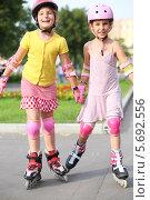 Купить «Две девочки катаются на роликах в парке», фото № 5692556, снято 8 июля 2013 г. (c) Losevsky Pavel / Фотобанк Лори