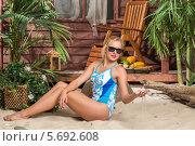 Купить «Красивая девушка в купальнике загорает на песчаном пляже», фото № 5692608, снято 3 октября 2013 г. (c) Losevsky Pavel / Фотобанк Лори