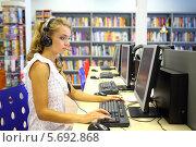Купить «Девушка в наушниках сидит за компьютером в библиотеке», фото № 5692868, снято 22 июля 2013 г. (c) Losevsky Pavel / Фотобанк Лори