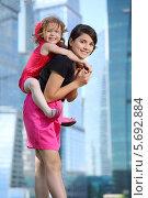 Купить «Красивая девушка с маленькой девочкой за спиной на фоне небоскребов», фото № 5692884, снято 21 июня 2013 г. (c) Losevsky Pavel / Фотобанк Лори