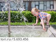Купить «Маленький мальчик плескается водой из фонтана в парке», фото № 5693456, снято 30 мая 2013 г. (c) Losevsky Pavel / Фотобанк Лори