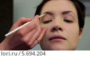 Купить «Стилист делает макияж бровей молодой женщине», видеоролик № 5694204, снято 10 февраля 2014 г. (c) Иван Артемов / Фотобанк Лори