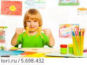 Купить «Улыбающийся малыш с бумажной гирляндой в руках», фото № 5698432, снято 23 ноября 2013 г. (c) Сергей Новиков / Фотобанк Лори