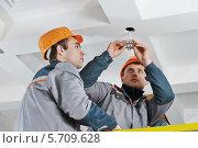 Купить «Два электрика чинят лампочку в потолке», фото № 5709628, снято 12 февраля 2014 г. (c) Дмитрий Калиновский / Фотобанк Лори