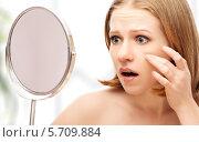 Купить «Испуганная девушка смотрит на свое лицо в зеркало», фото № 5709884, снято 13 марта 2014 г. (c) Евгений Атаманенко / Фотобанк Лори