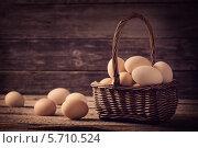 Купить «Яйца в корзинке на деревянном фоне», фото № 5710524, снято 11 марта 2014 г. (c) Майя Крученкова / Фотобанк Лори