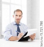 Купить «Успешный менеджер работает с документами, сидя за столом», фото № 5721780, снято 9 июня 2013 г. (c) Syda Productions / Фотобанк Лори