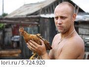 Купить «Молодой мужчина держит в руках курицу», эксклюзивное фото № 5724920, снято 13 августа 2012 г. (c) Вероника / Фотобанк Лори