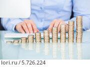Купить «стопки монет на фоне работающей на компьютере деловой женщины», фото № 5726224, снято 13 октября 2013 г. (c) Андрей Попов / Фотобанк Лори