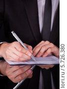 Купить «Бизмен пишет что-либо в документе», фото № 5726380, снято 19 октября 2013 г. (c) Андрей Попов / Фотобанк Лори