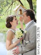 Купить «Жених и невеста в летнем парке, рядом с кормушкой для птиц», фото № 5728376, снято 10 мая 2013 г. (c) Losevsky Pavel / Фотобанк Лори