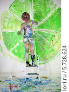 Купить «Полуобнаженная девушка, испачканная в краске, рисует лайм на стене», фото № 5728624, снято 11 мая 2013 г. (c) Losevsky Pavel / Фотобанк Лори