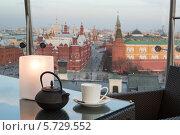Купить «Чайник, чашка и пепельница на столе в уютном кафе с видом на Красную площадь», фото № 5729552, снято 29 апреля 2013 г. (c) Losevsky Pavel / Фотобанк Лори