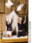 Купить «Красивая женщина и мужчина на бамбуковой кровати бросают подушки в спальне», фото № 5729840, снято 19 февраля 2013 г. (c) Losevsky Pavel / Фотобанк Лори