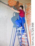 Купить «Рабочий в синем комбинезоне делает ремонт стены, стоя  на лестнице», фото № 5729944, снято 7 мая 2013 г. (c) Losevsky Pavel / Фотобанк Лори