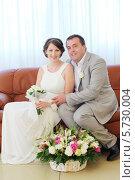 Купить «Жених и невеста сидят на диване перед корзиной цветов», фото № 5730004, снято 10 мая 2013 г. (c) Losevsky Pavel / Фотобанк Лори