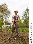 Купить «Позитивная блондинка с лопатой и граблями на грядках в весеннем саду», фото № 5734868, снято 25 мая 2013 г. (c) Евгений Ткачёв / Фотобанк Лори