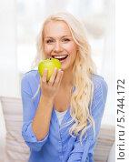 Купить «Красивая девушка смеется и держит в руках большое яблоко», фото № 5744172, снято 6 февраля 2014 г. (c) Syda Productions / Фотобанк Лори