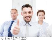 """Купить «Радостный бизнесмен показывает жест """"отлично"""" на фоне своих коллег», фото № 5744220, снято 9 июня 2013 г. (c) Syda Productions / Фотобанк Лори"""