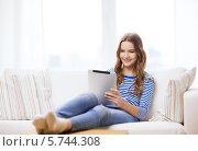 Купить «Улыбающаяся девушка лежит на диване дома и что-то смотрит на экране планшетного компьютера», фото № 5744308, снято 26 февраля 2014 г. (c) Syda Productions / Фотобанк Лори