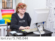 Пожилая женщина работает на компьютере в офисе. Стоковое фото, фотограф Кекяляйнен Андрей / Фотобанк Лори