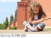 Маленькая кудрявая девочка сидит на фоне Кремлевской стены. Стоковое фото, фотограф Losevsky Pavel / Фотобанк Лори